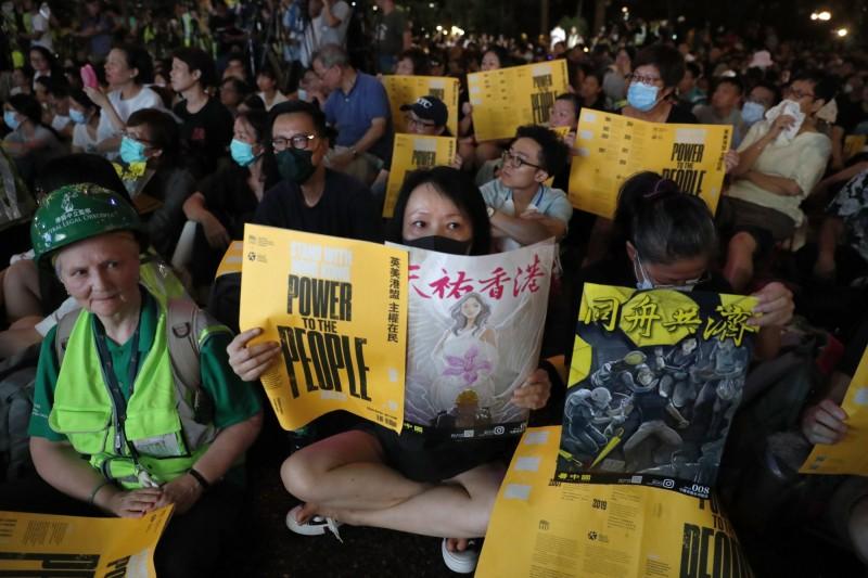 會場內有許多民眾舉起了本次「英美港盟,主權在民」活動的黃色海報。(歐新社)