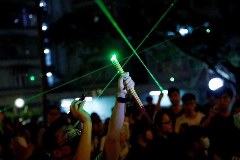 有港人9日在黃大仙港舉辦「燒衣大會」時拿出雷射筆,並以驅走「牛鬼蛇神」諷刺港府。(路透)