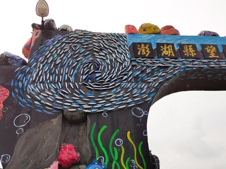 大門牌樓上快樂游動的魚群,是海廢浮球製作。(吳成夫提供)