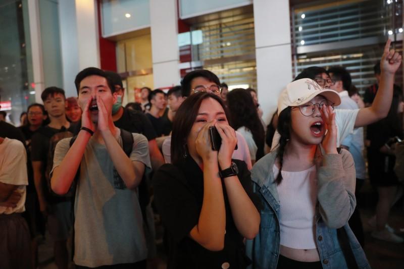 香港示威民眾今日遊行未配戴任何防護配備,在路邊呼喊「黑警撤退」、「聽日見」(明天見)。(歐新社)