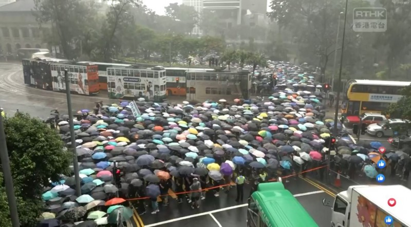 香港教協發起教育界遊行,現場下起滂沱大雨,但仍有源源不絕的人流自遮打花園湧出。(擷取自《香港電台》直播畫面)