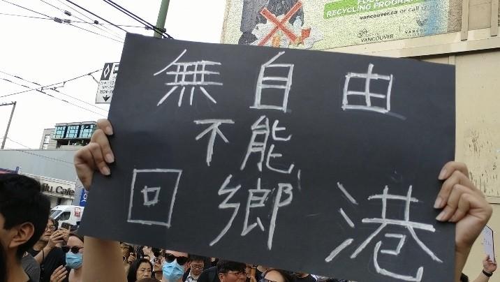 香港移民持「無自由不能回鄉港」的標語。(臉書照片)
