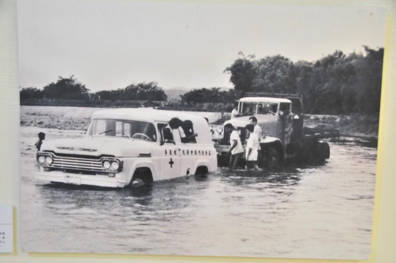 早期門諾會的巡迴醫療車是以美軍卡車改裝,經常得涉水過溪,圖為醫療車在過溪途中拋錨,人員只好下車推車。(資料照,記者花孟璟翻攝)