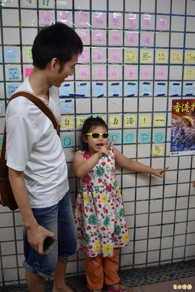 爸爸帶著女兒,到「連儂牆」體驗公民課。(記者張瑞楨攝)