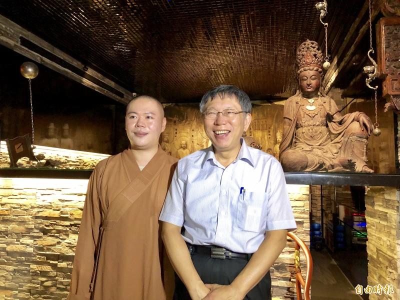 台北市長柯文哲(右)進入佛寺後,在宏願大千世界住持釋本藏(左)陪同下參觀。(記者魏瑾筠攝)