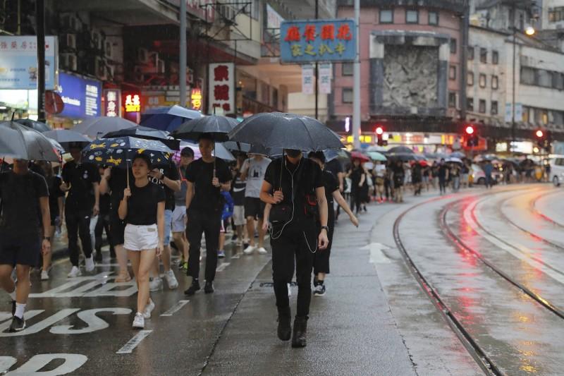 下起大雨,市民撐起雨傘繼續參與集會。(美聯社)<br /><p>