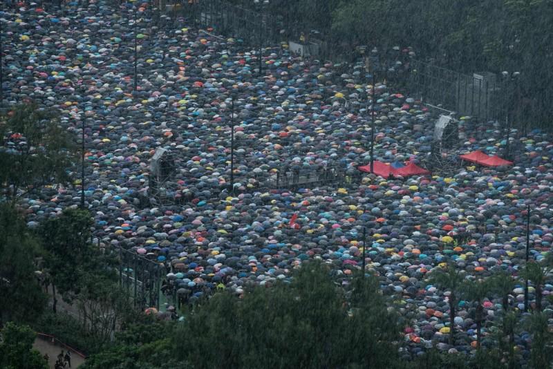 下午3時許,現場下起傾盆大雨,維園內群眾開傘避雨。(法新社)