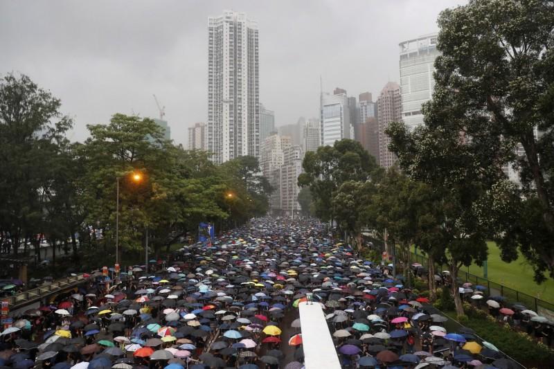 民陣啟動「流水式」疏導措施,由民主派議員帶領部分群眾由一旁的高士威道離場。(歐新社)