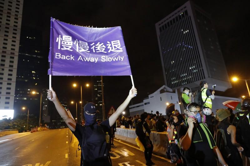 有人舉起「慢慢後退」的藍色旗幟,呼籲民眾回家。(美聯社)