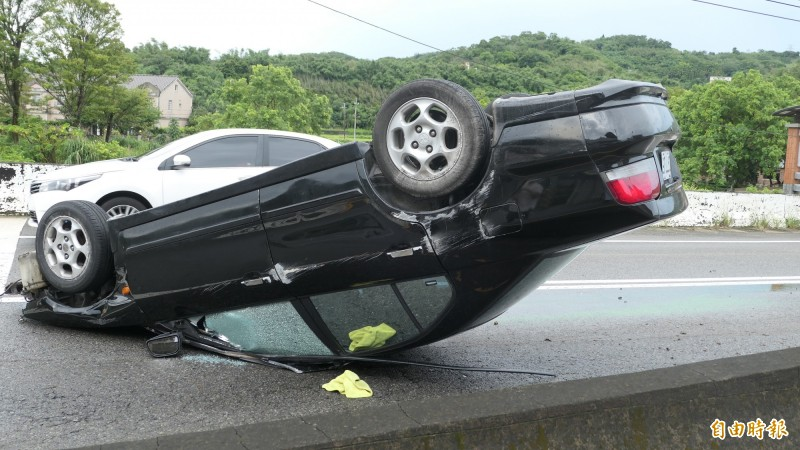 李男駕駛小客車衝撞護欄,四輪朝天。(記者張勳騰攝)