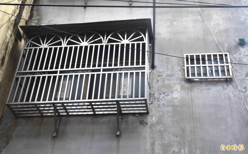 透天厝2樓外一大一小的鐵窗,成了少女與外界聊天、用繩子收受物品的窗口。(記者李容萍攝)