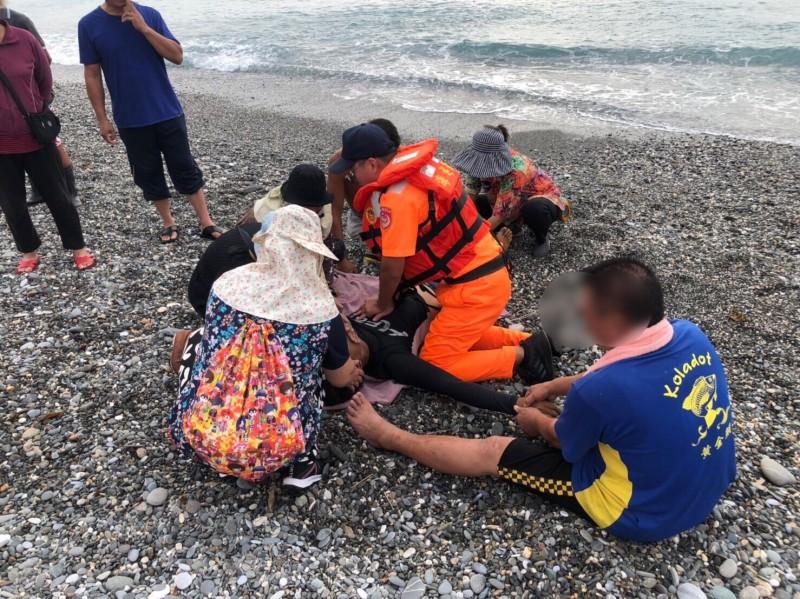 王男被釣客拖救上岸已無生命跡象,海巡人立即給予CPR,在旁家屬不斷搓揉王男手腳,悲慟不已。(記者陳賢義翻攝)