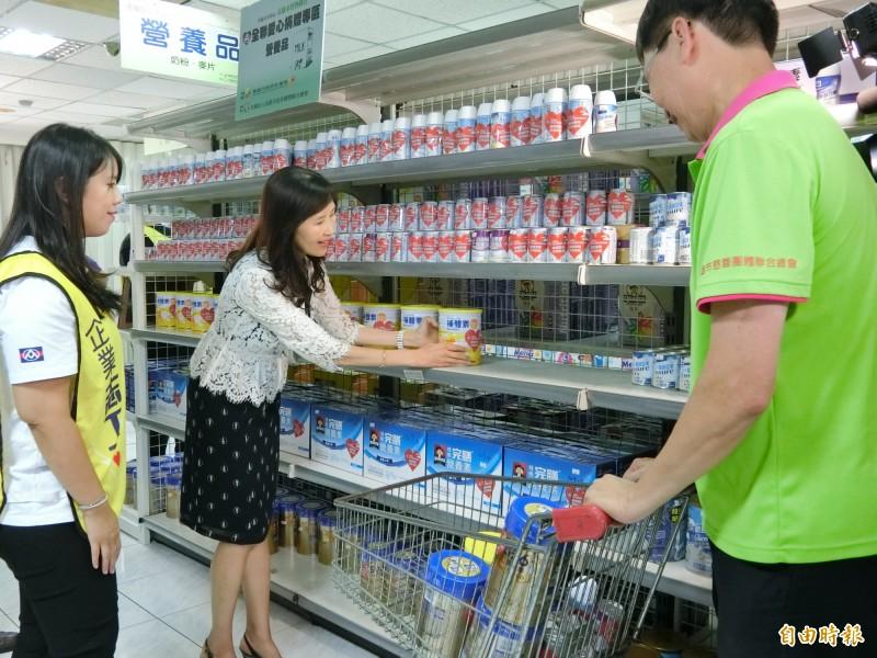 志工協助擺設實物銀行商品。(記者黃旭磊攝)