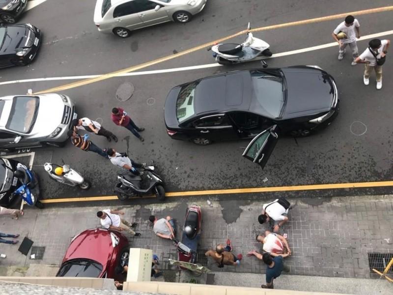 車手駕駛黑色汽車,警察開槍破窗,將2名車手抓道路旁(圖左,蹲坐地上者)。(記者張瑞楨翻攝自江肇國臉書)