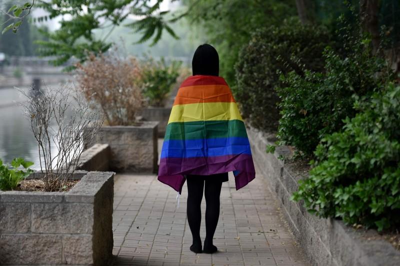 中國人大法工委發言人臧鐵偉今(21)日表示,中國將維持一夫一妻、一男一女的婚姻制度。圖為中國學生在北京批上彩虹旗。(法新社)
