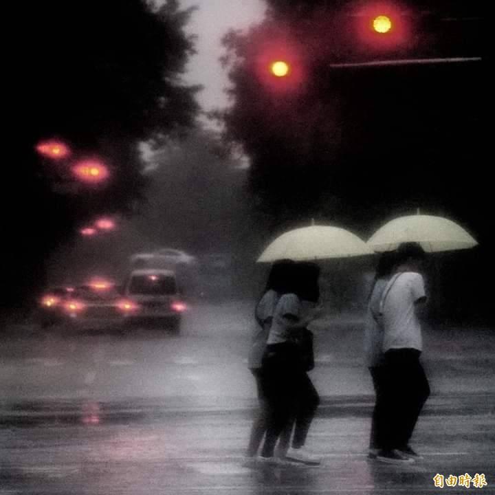 瞬間暴雨讓學生們緊挨著彼此,撐傘緩步慢行。(記者鹿俊為攝)