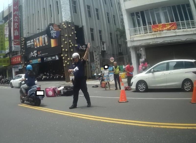 美食外送員今發生車禍,警方到場疏導交通,救護人員評估傷者傷勢,將2名騎士送醫救治。(記者王善嬿翻攝)