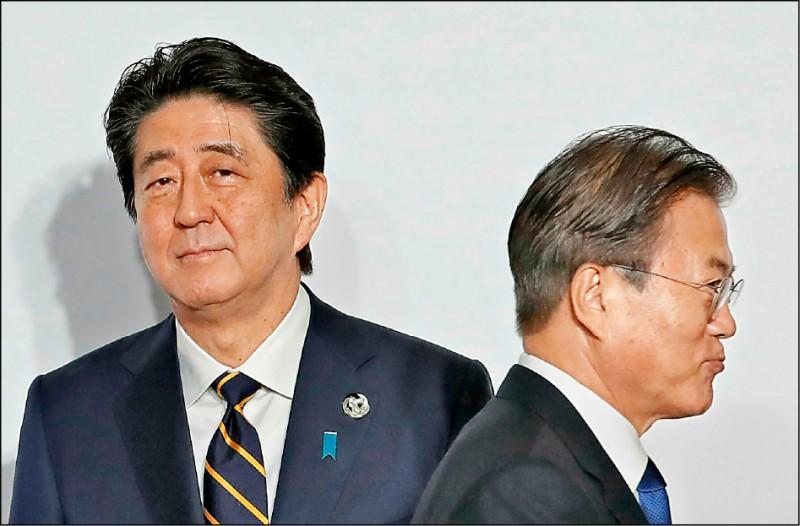 日本首相安倍晉三(左)六月間以大阪二十國集團(G20)高峰會東道主身分,向出席峰會的南韓總統文在寅致意,兩人表情僵硬。(美聯社檔案照)