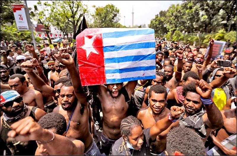 巴布亞抗議者在雅加達手舉象徵分離主義的「晨星旗」,抗議印尼警方日前逮捕西巴布亞省學生,以種族歧視字眼辱罵他們。(美聯社)