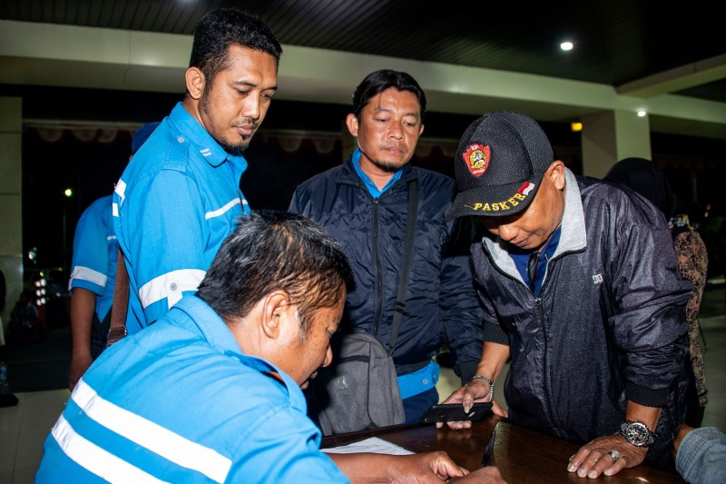 印尼一艘渡輪在爪哇島海岸附近發生大火,圖為在丹戎佩拉港等待接收遇難家人情報的乘客家屬。(法新社)