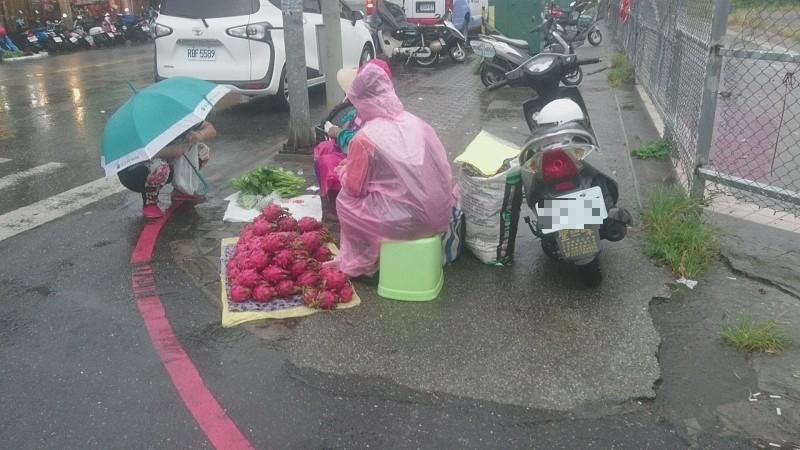 自產自銷果菜農冒著風雨擺攤,路經民眾不捨蹲身購買。(記者陳賢義翻攝)