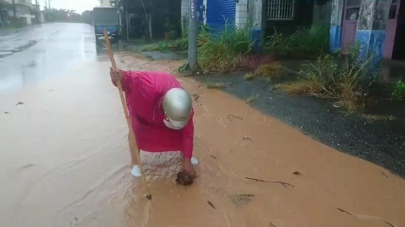 泥流淹過路面,婦人自行清除落葉斷枝。(記者陳賢義翻攝)