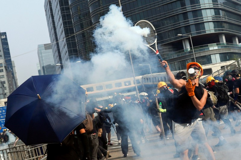 示威者手持網球拍回擊催淚彈的瞬間,被記者拍下,照片傳至網路後掀起一陣討論。(路透)