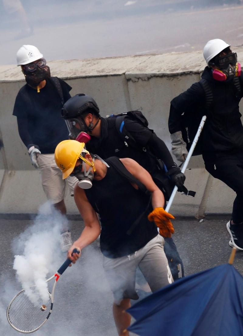 一名示威者多次以網球拍回擊港警發射的催淚彈。(路透)