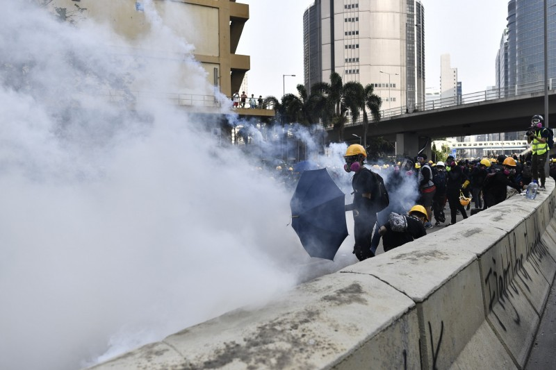 警方舉出黑旗,並射出多發催淚彈試圖驅離群眾。(法新社)
