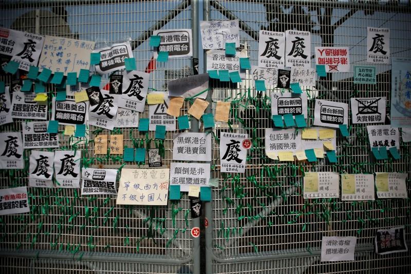 親中派人士前往《香港電台》抗議,在外牆貼滿標語並掛上綠絲帶。(路透)