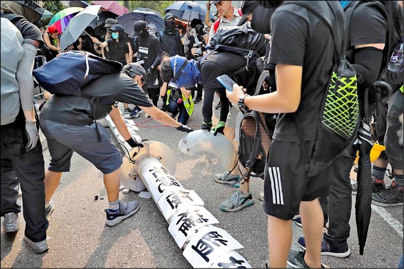 香港觀塘區24日遊行期間,示威民眾在「智慧燈柱」的柱身貼上「拒絕極權監控」等字句,並當街直接拉倒燈柱。(美聯社)