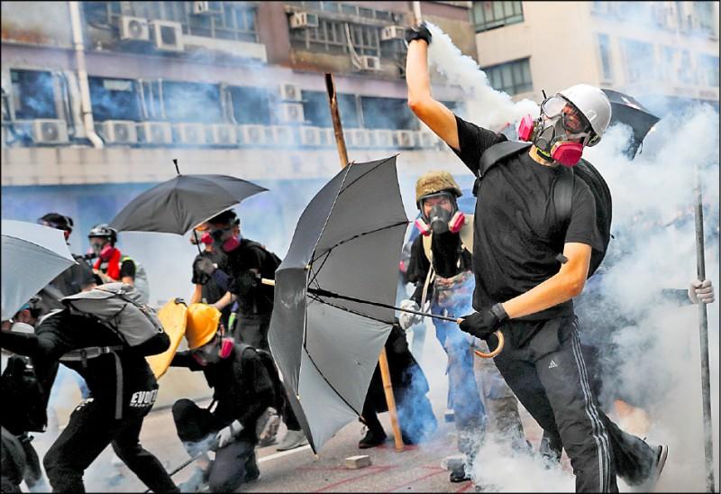 香港觀塘區24日爆發激烈警民衝突,示威民眾徒手將催淚彈丟回給警察。(路透)