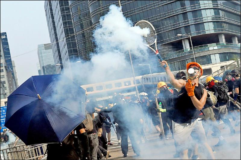 香港觀塘區24日警民衝突期間,一名示威者驚險用網球拍將催淚彈擊回給鎮暴警察。(路透)