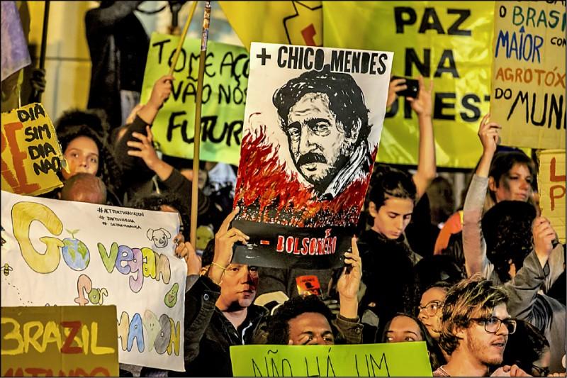 關心巴西亞馬遜雨林大火的巴西國內外人士,紛紛走上街頭,抗議巴西總統波索納羅的環境政策與相關發言。圖為23日巴西里約熱內盧的一場示威抗議,有示威者舉起已故巴西環保主義者、保護亞馬遜雨林不遺餘力的孟迪斯(Chico Mendes)畫像。(彭博)