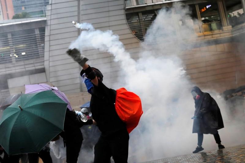 香港反送中抗爭者二十五日在荃灣與警方爆發衝突,一名示威者將警方發射的催淚彈擲回去。(路透)
