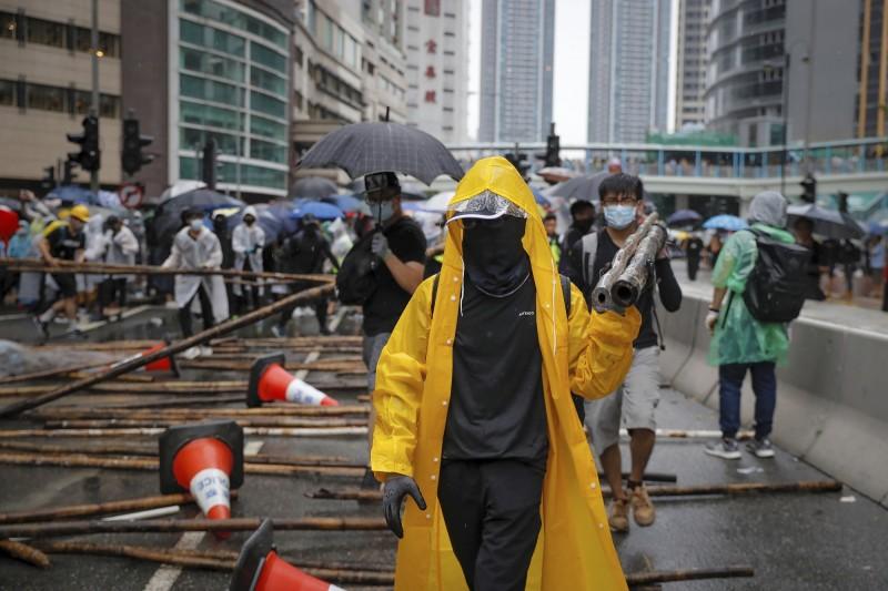 示威者以鐵欄及竹竿築起防線,警方舉出黃旗警告行為違法。(美聯社)