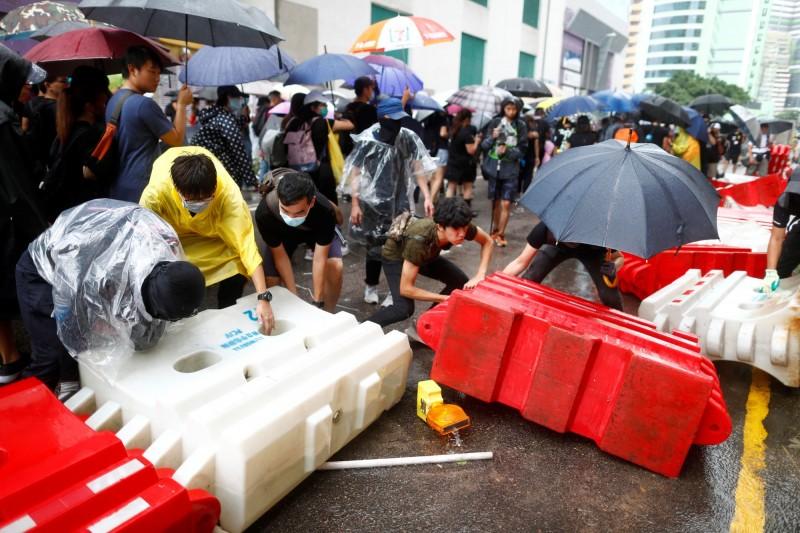 部分示威者搬移水馬(充水式護欄)以架起防線。(路透)