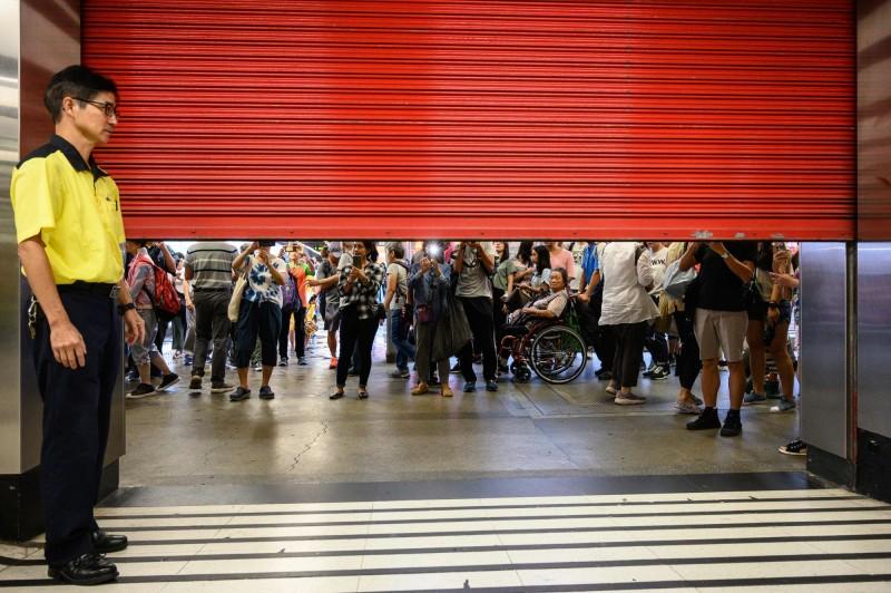 香港今(25日)下午將展開荃葵青大遊行,港鐵竟在先行關閉葵芳站、荃灣站、荃灣西站,不過過程中並不順利,因為民眾紛紛阻止讓鐵門拉下。(法新社)