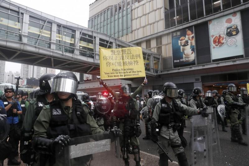 警方舉出黃旗,警告示威者行為違法。(歐新社)