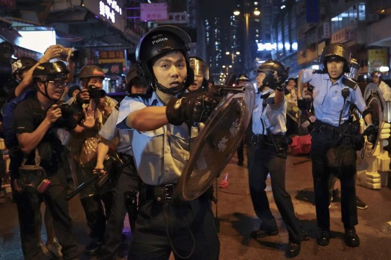晚間8點左右,傳出有6名港警遭示威者包圍,現場至少有3人拔槍指向示威者。(美聯社)