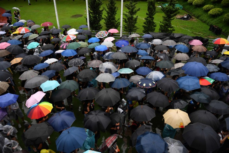 遊行提早數分鐘出發,現場下著大雨,但並未澆熄民眾熱情。(法新社)