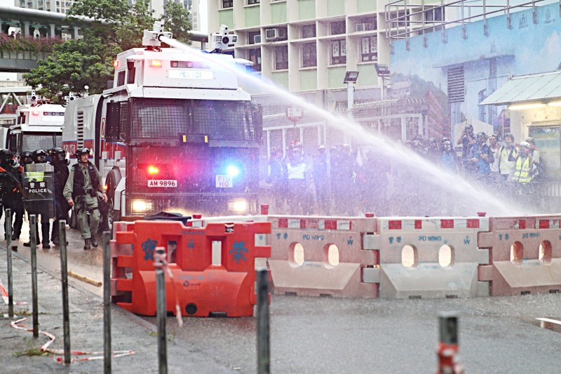 A police vehicle equipped with a water cannon clears a road of barricades set up by protesters during a rally in Hong Kong's New Territories yesterday. Photo: EPA-EFE