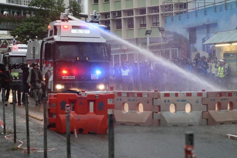 警方嘗試用水砲車的水柱衝擊示威者設下的路障,不過未能成功。(歐新社)