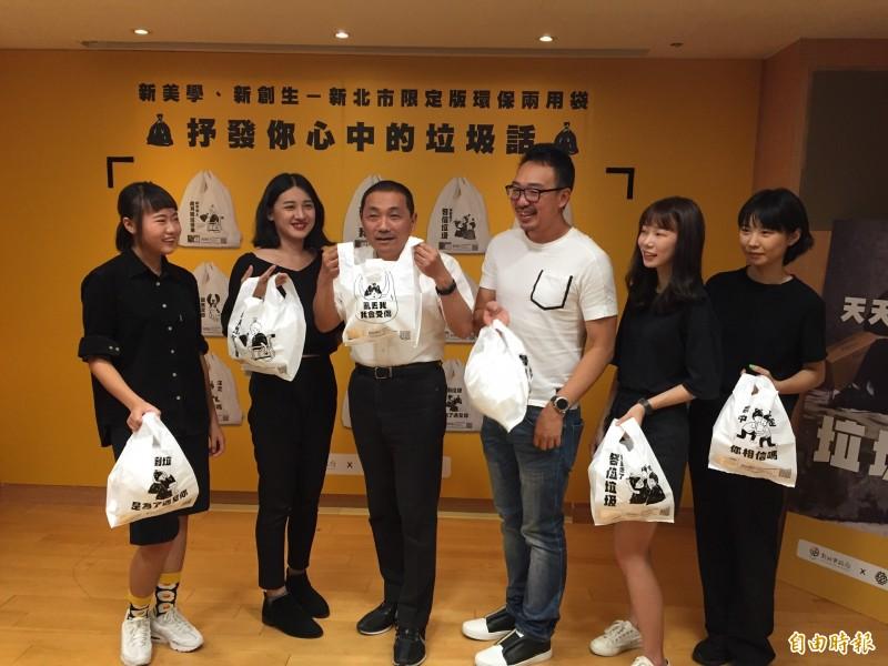 侯友宜相當喜愛這次的文創垃圾袋,和設計的4位大學生及指導老師李尉郎(右2)合影。(記者邱書昱攝)