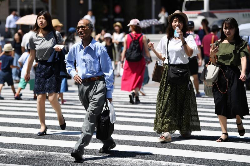 日本東京傳出一對老夫婦陳屍在屋內,疑似是中暑喪命。圖為在東京8月烈日下走過街頭的民眾。(法新社)