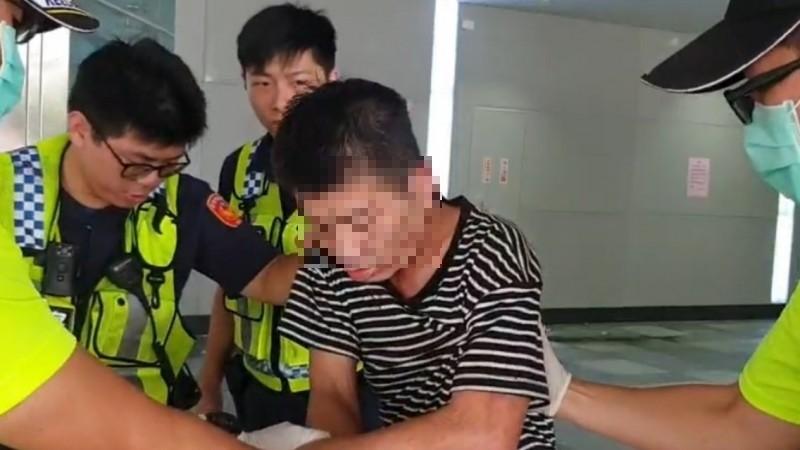 遭刺傷腿部的遊民,因失血過多,臉部發白,警消合力將他送醫救治。(記者林嘉東翻攝)