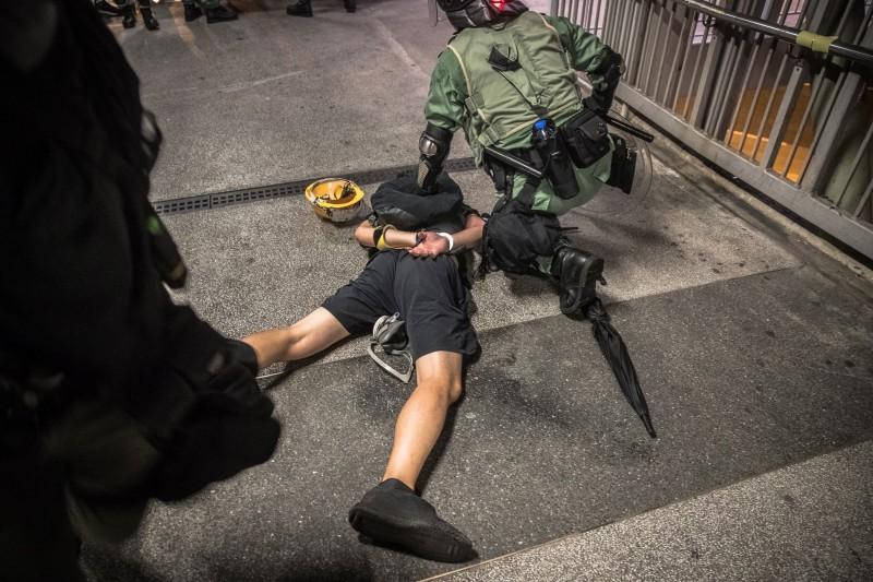 香港反送中運動自6月至今,香港警察共拘捕近900人。圖為24日的觀塘遊行,鎮暴警察開始抓捕示威者。(歐新社)