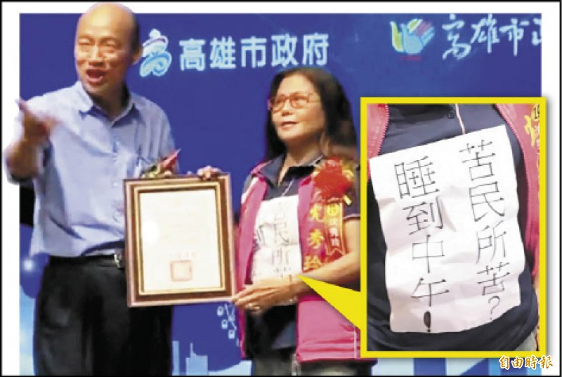 高雄市長韓國瑜(左)昨表揚特優暨資深里長,正興里長沈秀玲(右)領獎時胸前貼著「苦民所苦?睡到中午!」貼紙,表達對韓不滿。(記者洪臣宏攝)