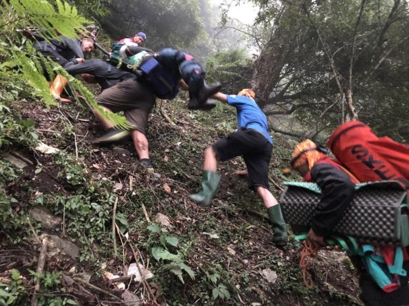 女大生在玉山八通關古道墜谷,搜救人員爭取時效,下到40米深谷將受傷女大生揹負回步道。(記者劉濱銓翻攝)