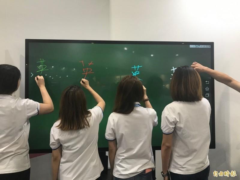 宸鴻光電今展示大型互動電子白板,就示範用觸控筆寫整排「英」字,似乎暗諷昨天群創凸槌一事。(記者陳梅英攝)